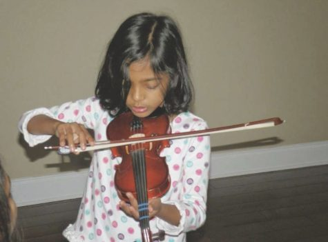 Nadia Priyam playing violin as a child